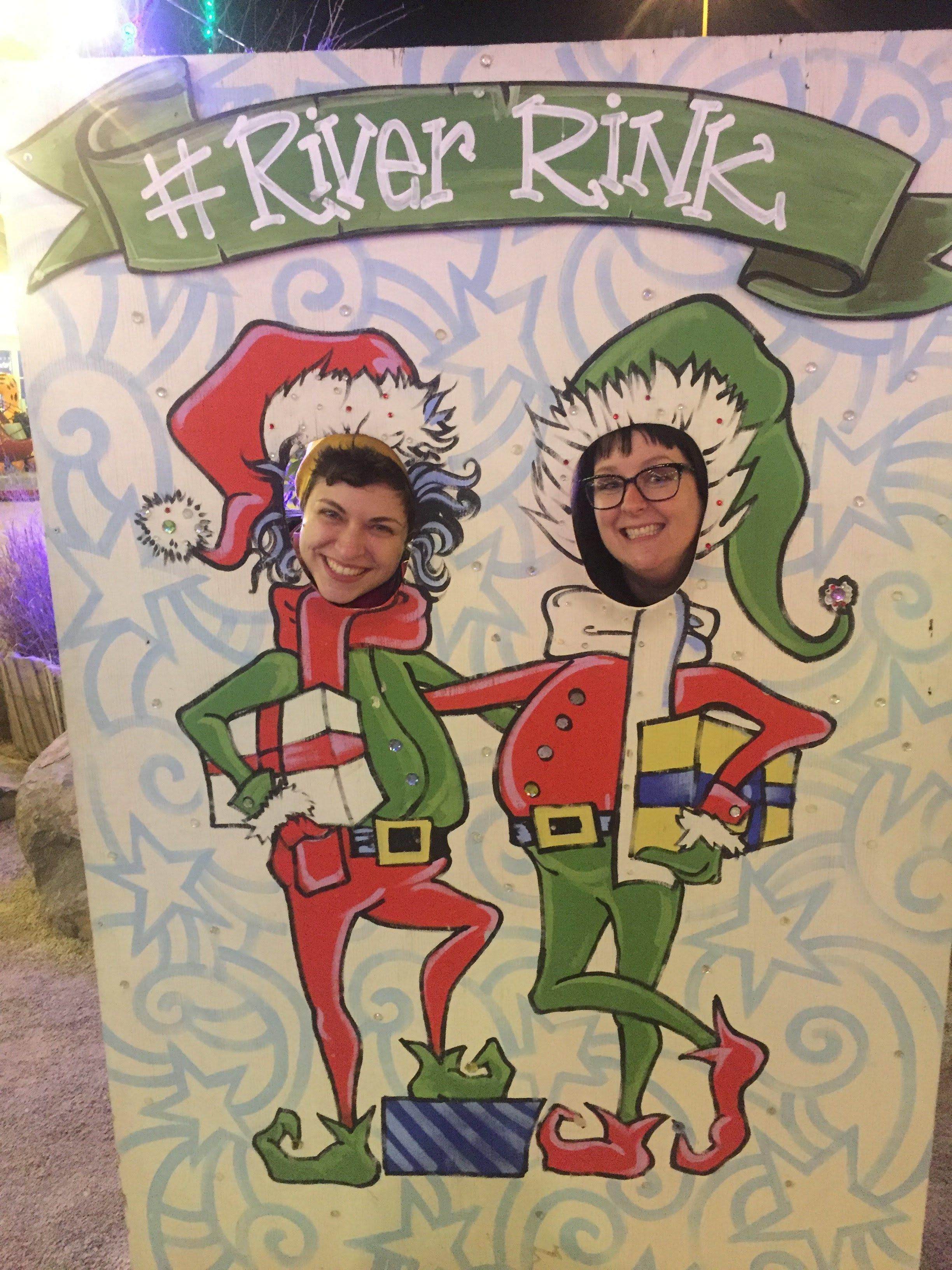 Two people in a holiday themed face in hole.