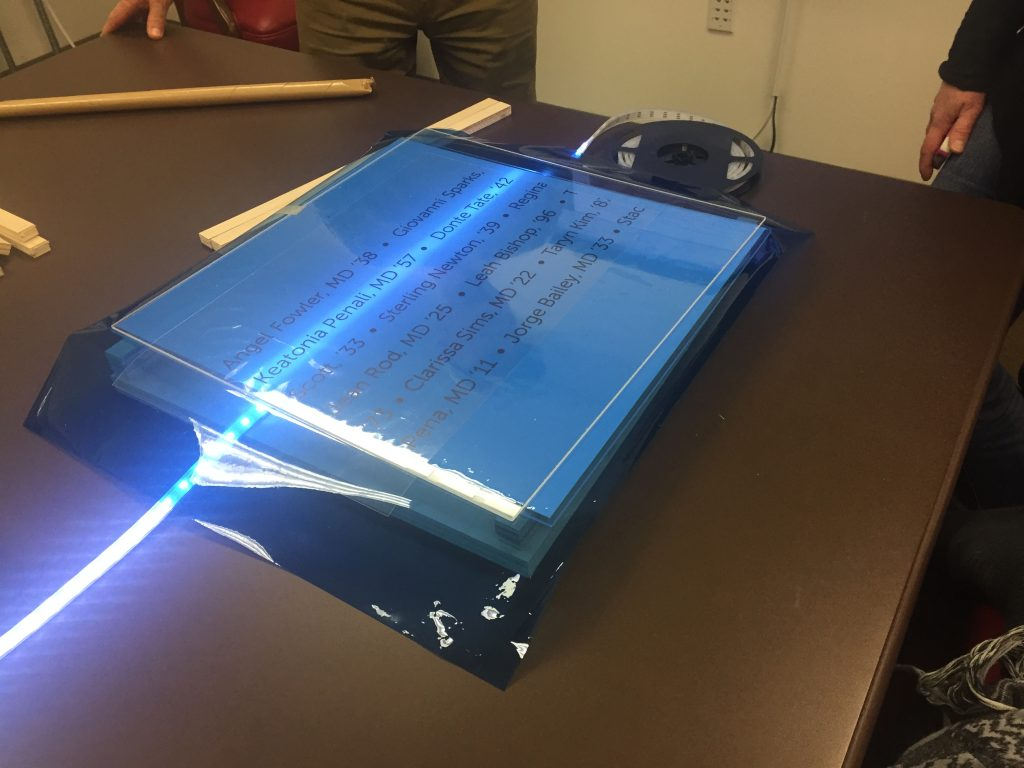 Prototype of a wall with a list of names, one backlit by LED lights