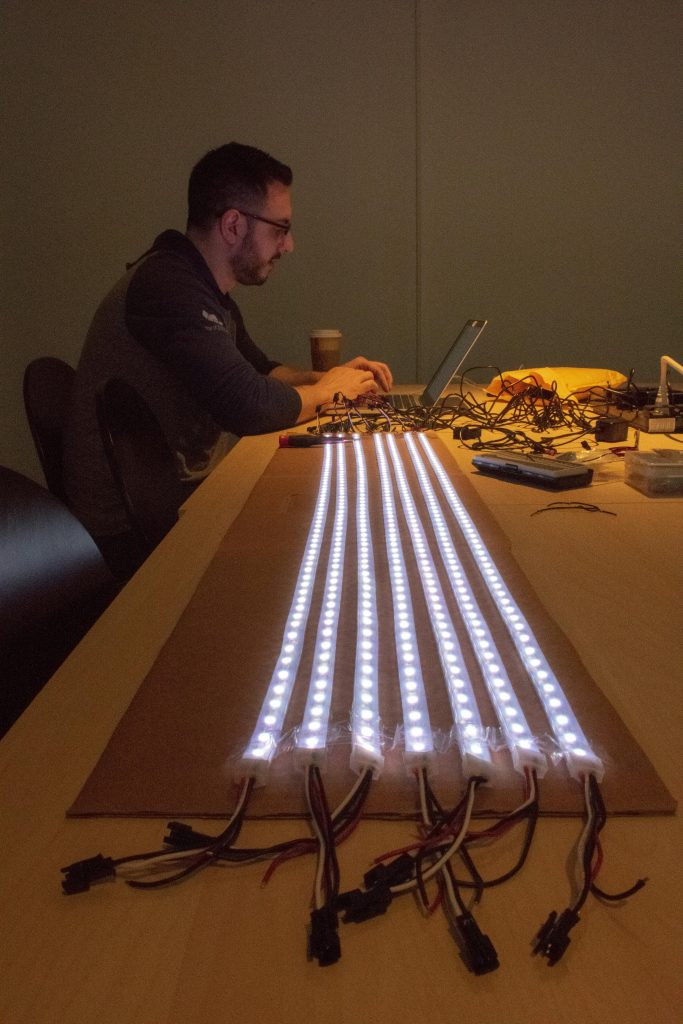 A man at a laptop programming LED strips
